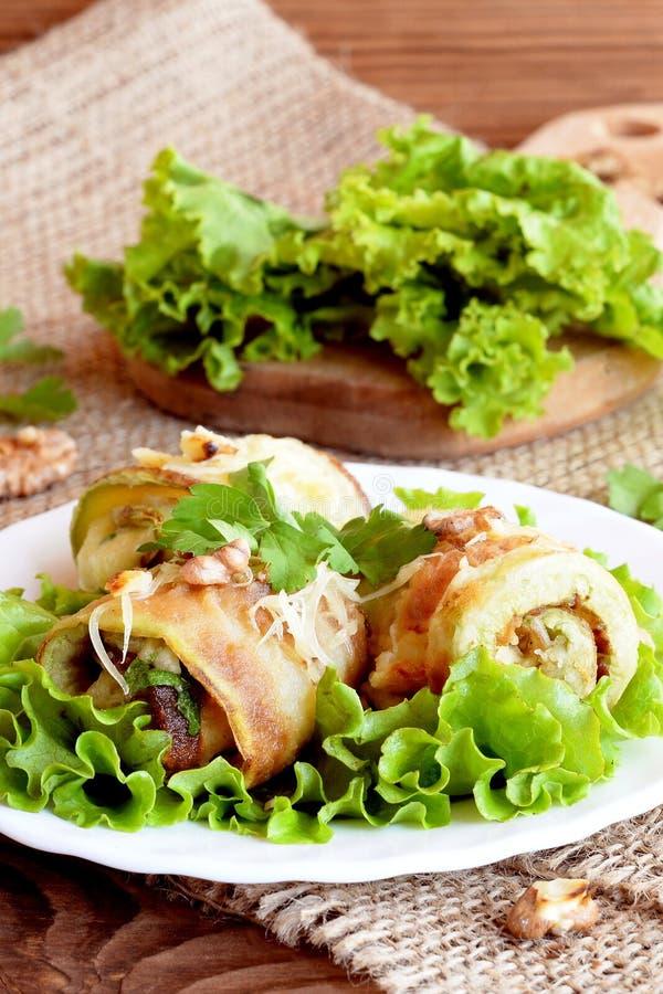 Den stekte zucchinin rullar med ost, valnötter och örter Nya grönsallatsidor på ett träbräde arkivbilder