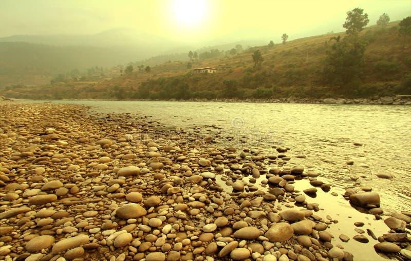 Den steniga flodstranden med gloden soluppgång i morgonen arkivbilder