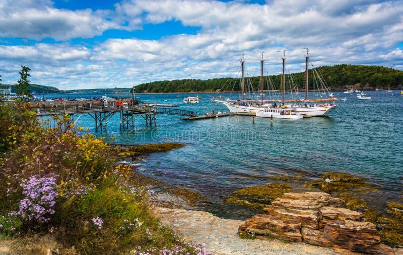 Den steniga kusten och sikten av fartyg i hamnen på stången härbärgerar, Maine royaltyfria bilder