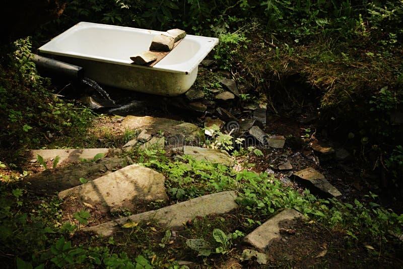 Den steniga trappan som leder till det gamla badkar- och gummiröret i liten skog, strömmar arkivbilder