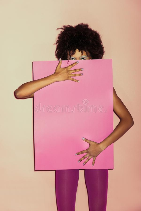 den stilfulla afrikansk amerikan80-talflickan i rosa kläder som rymmer rosa färger, skyler över brister royaltyfri bild