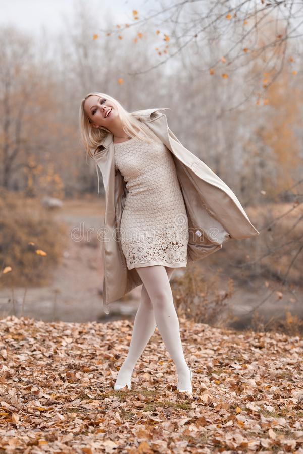 Den stilfulla blonda kvinnan i hösten parkerar arkivfoto