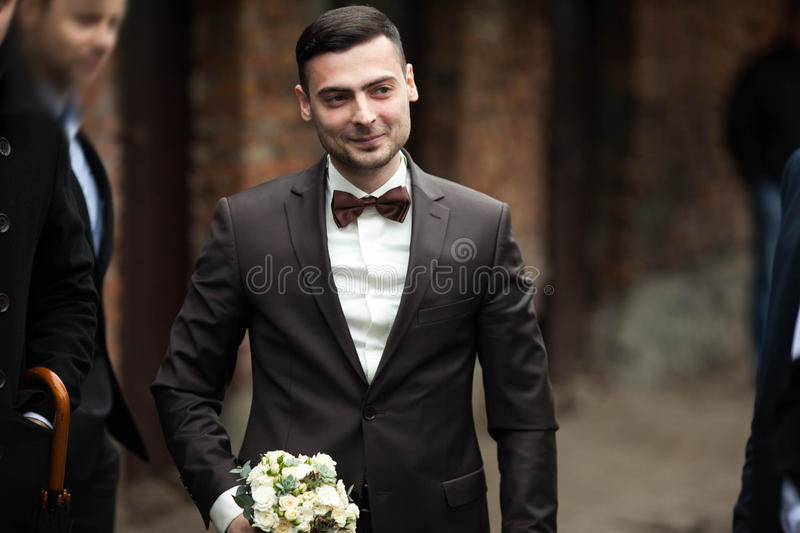 Den stilfulla brunetten som ler brudgummen i en dräkt med en brun pilbåge, rymmer royaltyfri bild