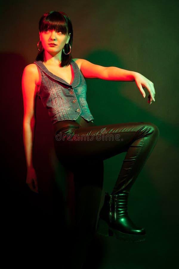 Den stilfulla brunettkvinnan i läder flåsar i rött och klartecken royaltyfri fotografi