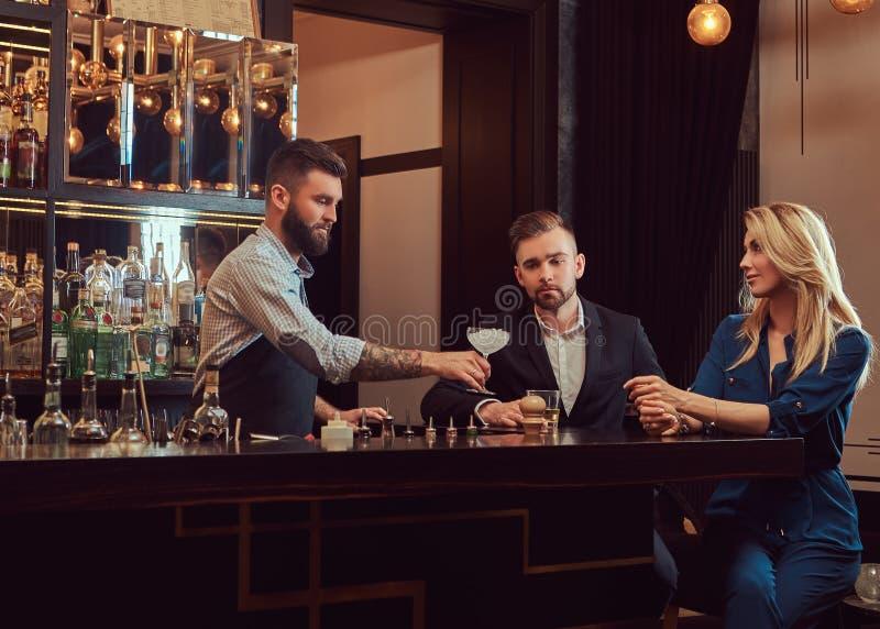 Den stilfulla brutala bartendern tjänar som ett attraktivt par som spenderar en afton på ett datum arkivfoton
