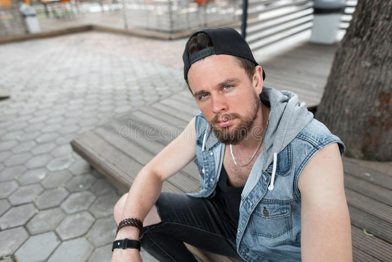 Den stilfulla brutala unga mannen som hipsteren med ett skägg i en T-tröja i sönderriven jeans i moderiktig jeans tilldelar ett t fotografering för bildbyråer