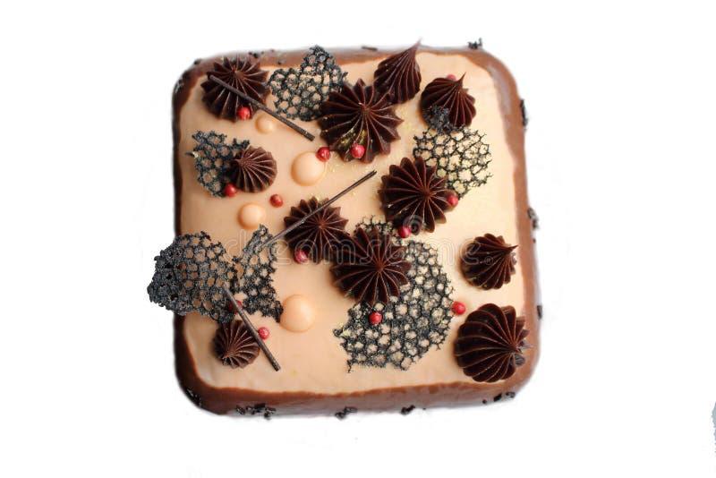 Den stilfulla choklad- och karamellkakan med ganache, rosa peppar och svart sn?r ?t royaltyfri fotografi