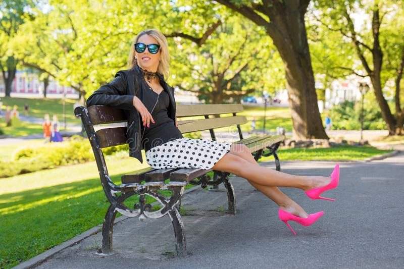 Den stilfulla flickan med rosa höga häl som sitter på bänk parkerar in arkivfoton