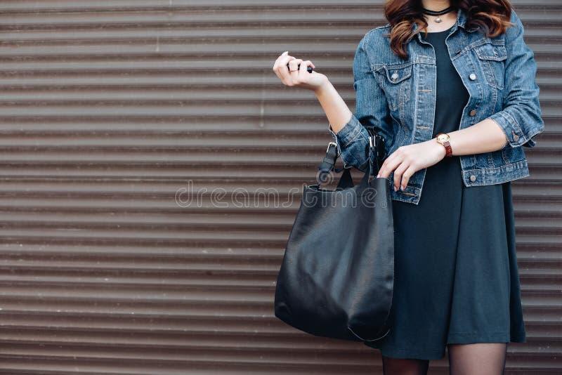 Den stilfulla flickan som poserar på gatan med svart, piskar inkognito påsen royaltyfria bilder
