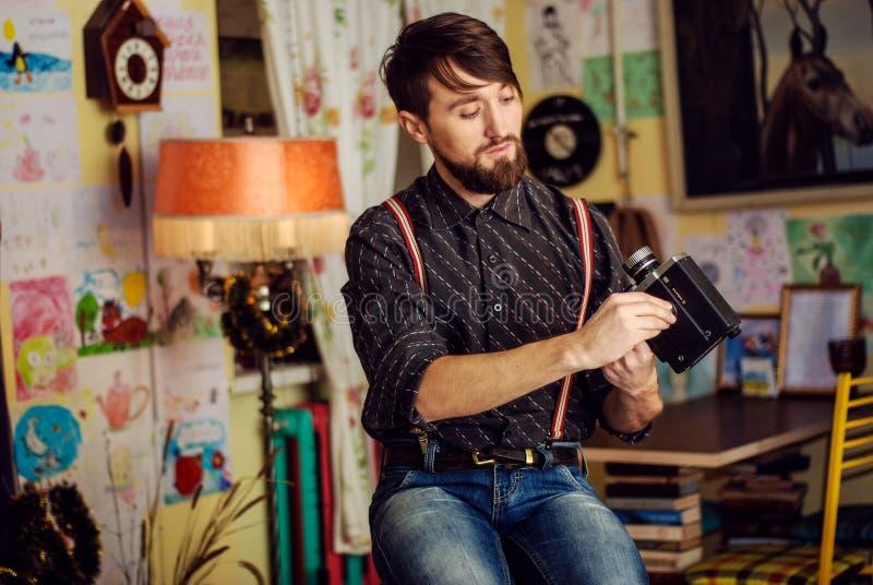 Den stilfulla hipsteren uppsökte mannen som rymmer den gamla filmkameran arkivbilder