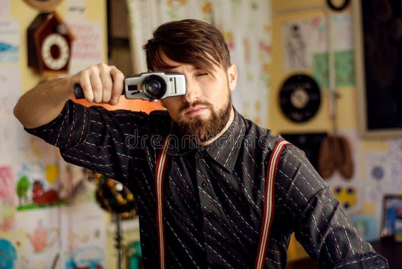 Den stilfulla hipsteren uppsökte mannen som rymmer den gamla filmkameran royaltyfri foto