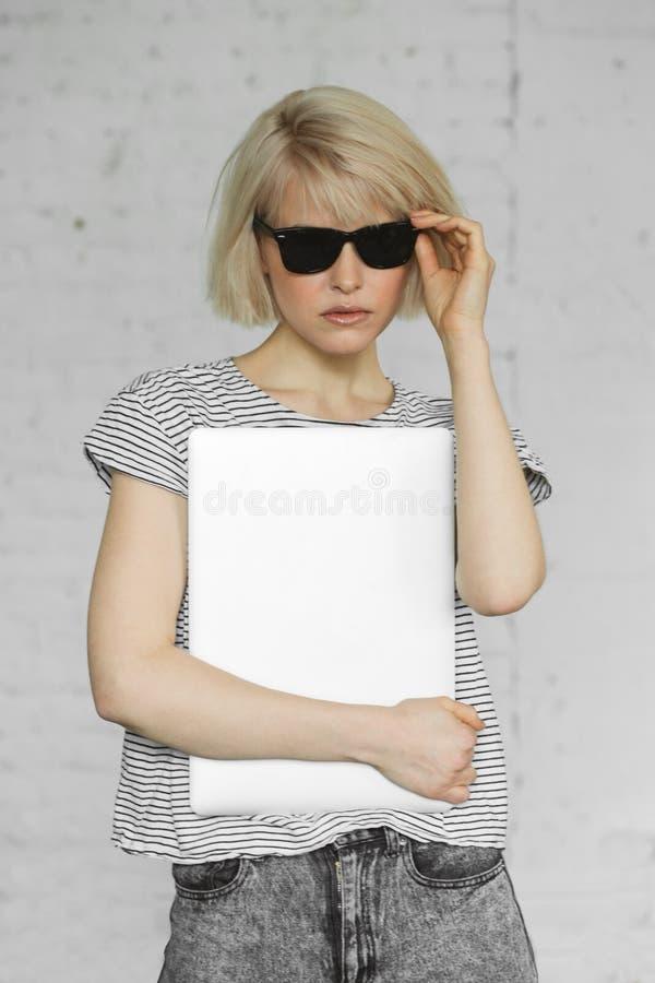 Den stilfulla Hipsterflickan bär solglasögon och rymmer bärbara datorn på dagsljus fotografering för bildbyråer