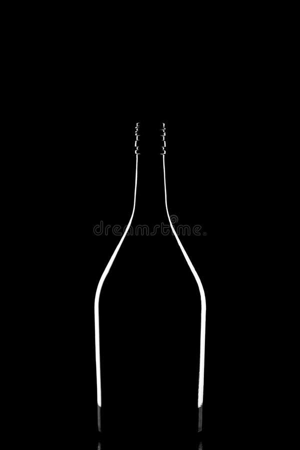 Den stilfulla konturn av den eleganta svarta korkade vinflaskan reflekterade och skisserade vid ljus på svart bakgrund arkivbilder