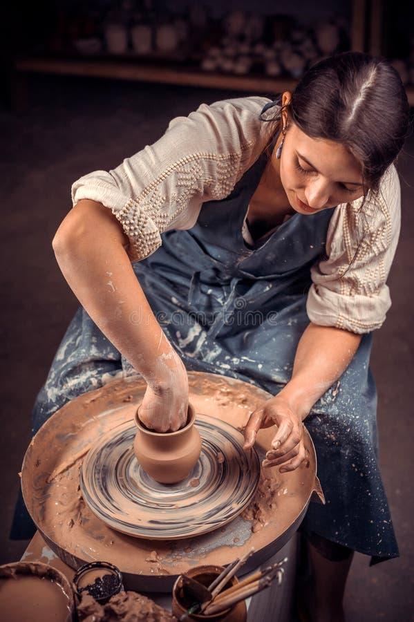 Den stilfulla kvinnliga förlagen visar processen av att göra keramisk disk genom att använda den gamla teknologin Framst?llning a arkivbild