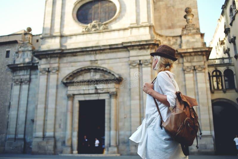 Den stilfulla kvinnliga utlänningen undersöker den arkitektoniska monumentet under hennes lång-väntade på sommarsemester royaltyfri bild