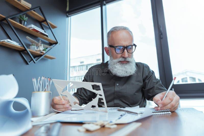 Den stilfulla mogna teknikern arbetar på hans byggnadsplan arkivfoto