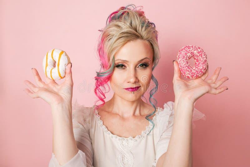 Den stilfulla och härliga kvinnan med kulört hår med två donuts, glamourrosa färger utformar royaltyfri foto