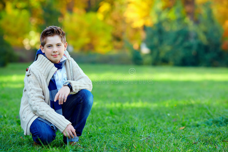 Den stilfulla tonårs- pojken i gräsplan parkerar fotografering för bildbyråer