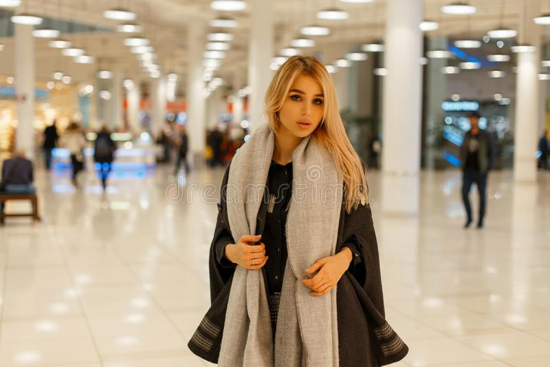 Den stilfulla unga blonda kvinnan i ett lyxigt moderiktigt hösttappninglag med en trendig varm halsduk går att shoppa arkivbild