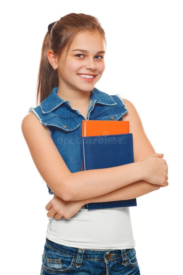 Den stilfulla unga flickan i jeans väst och grov bomullstvill kortsluter med böcker i händer Skolflicka med läroböcker Gatastilto fotografering för bildbyråer