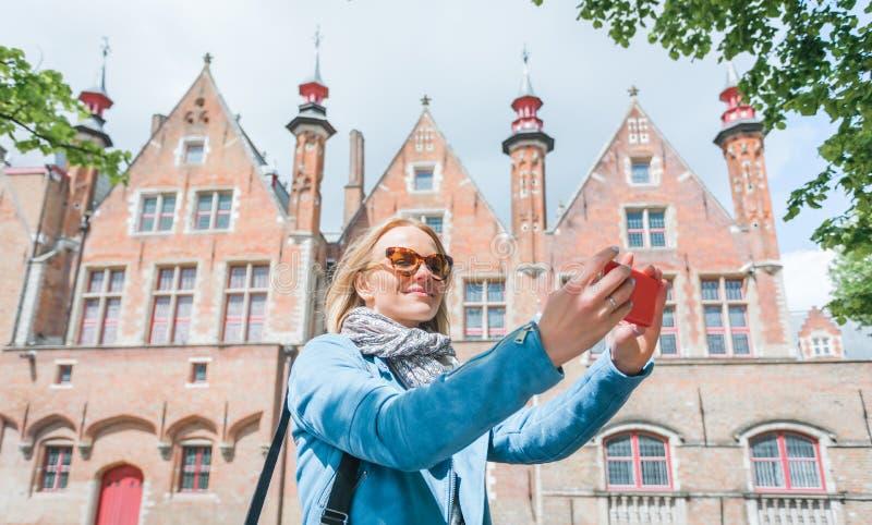 Den stilfulla unga kvinnliga turisten tar en selfie på en mobiltelefon i Bruges, Belgien arkivfoto