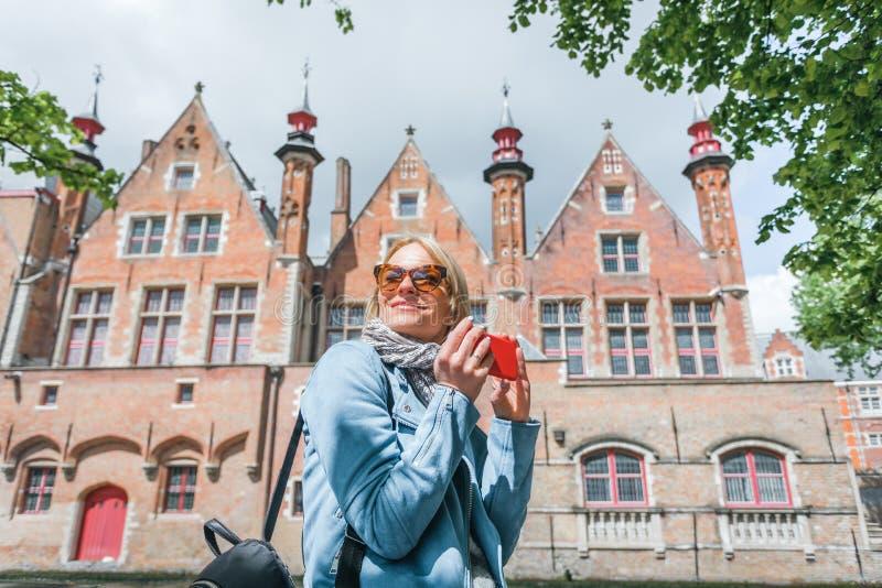 Den stilfulla unga kvinnliga turisten tar en selfie på en mobiltelefon i Bruges, Belgien royaltyfri fotografi