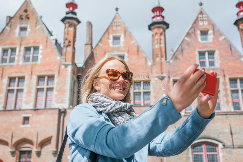 Den stilfulla unga kvinnliga turisten tar en selfie på en mobiltelefon i Bruges, Belgien arkivbilder