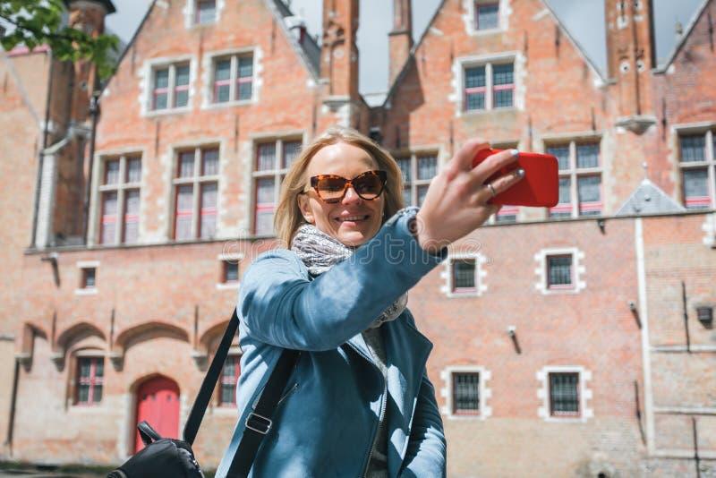 Den stilfulla unga kvinnliga turisten tar en selfie på en mobiltelefon i Bruges, Belgien royaltyfri bild