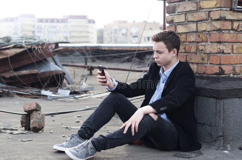 Den stilfulla unga mannen med telefonen läser meddelandet royaltyfri foto