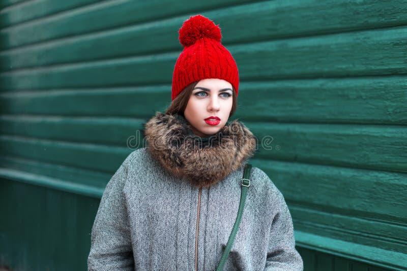 Den stilfulla unga ryska flickan i trendig vinter beklär standinen royaltyfri foto