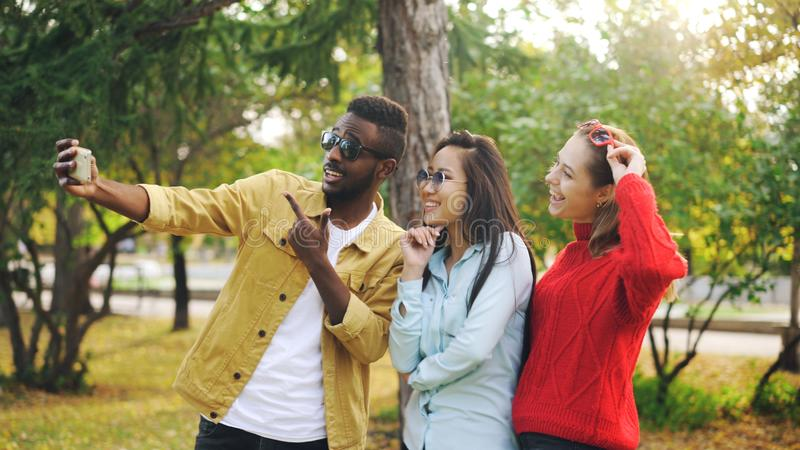Den stilfulla ungdomarmannen och kvinnor tar bärande solglasögon för selfie som poserar och ler den hållande smartphonen under royaltyfri foto