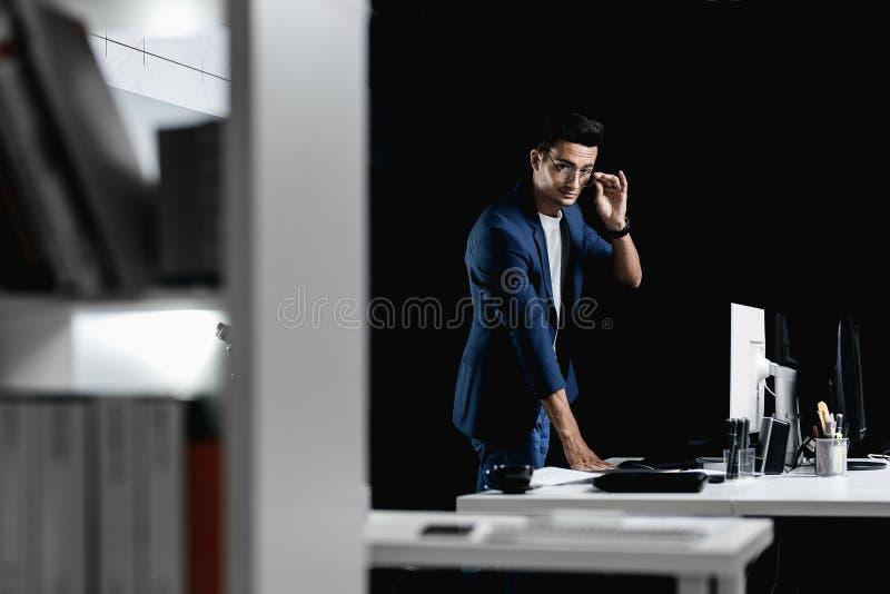 Den stilfulla yrkesmässiga arkitekten i iklädda exponeringsglas ett blått rutigt omslag står bredvid skrivbordet med datoren in arkivbilder