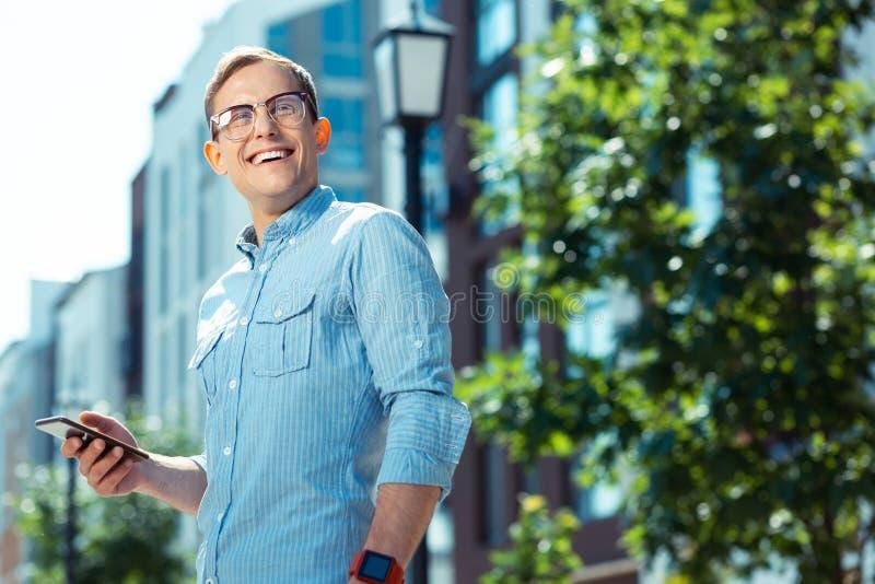 Den stiliga affärsmannen som i huvudsak ler, medan tycka om helg, går arkivbilder