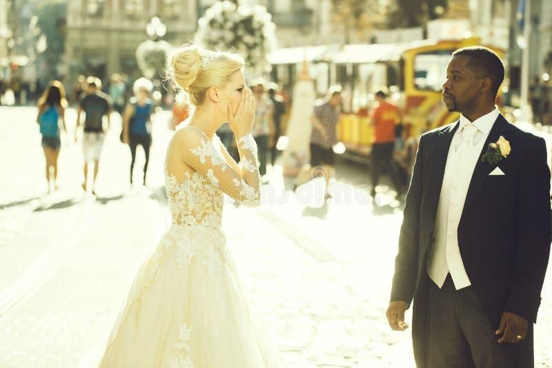 Den stiliga afrikansk amerikanbrudgummen ser den gulliga bruden royaltyfri fotografi