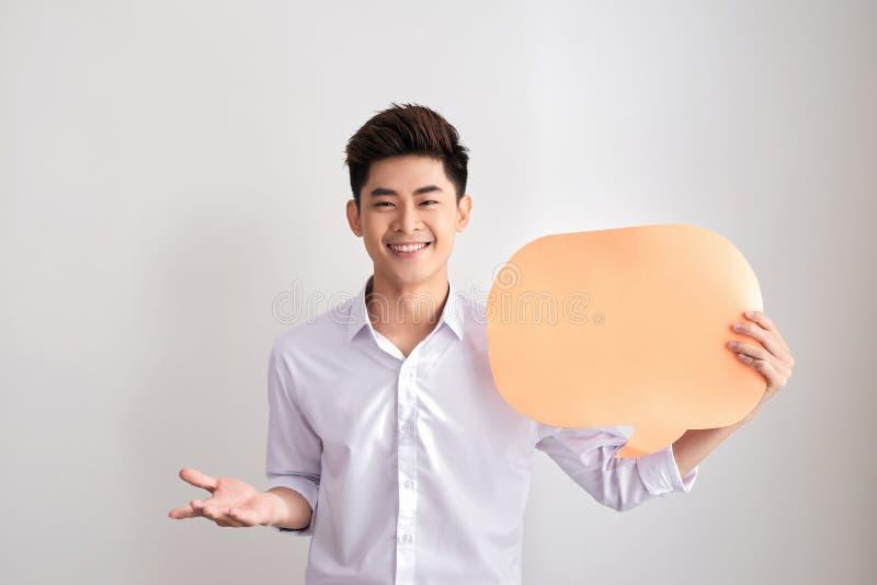 Den stiliga asiatiska mannen i klassisk skjorta rymmer en bubbla och le f?r anf?rande som st?r p? den vita v?ggen arkivbild