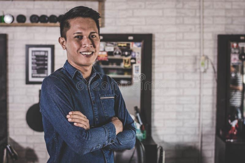Den stiliga asiatiska mannen korsade hans arm framme av frisersalongstol royaltyfria foton