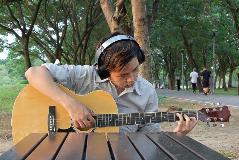 Den stiliga asiatiska unga mannen med headphonen spelar den akustiska gitarren i stad parkerar royaltyfria bilder
