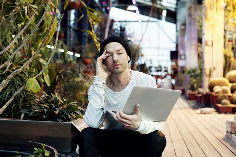 Den stiliga attraktiva hipstermannen tröttade på arbete som sitter utanför i en parkera med bärbar datordatoren Affärslivsstilbeg royaltyfria bilder