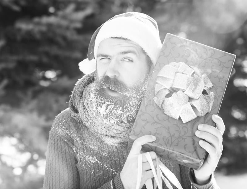 Den stiliga blinka mannen i den Santa Claus hatten, skäggig hipster med skägget och mustaschen som täckas med vit frost, rymmer r royaltyfria foton