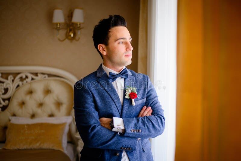 Den stiliga brudgummen korsar hans händer på bröstkorgen fotografering för bildbyråer