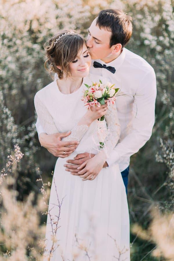Den stiliga brudgummen rymmer försiktigt den hållande buketten för brudbaksida och den kyssande pannan i den blomstra vårträdgård royaltyfri foto