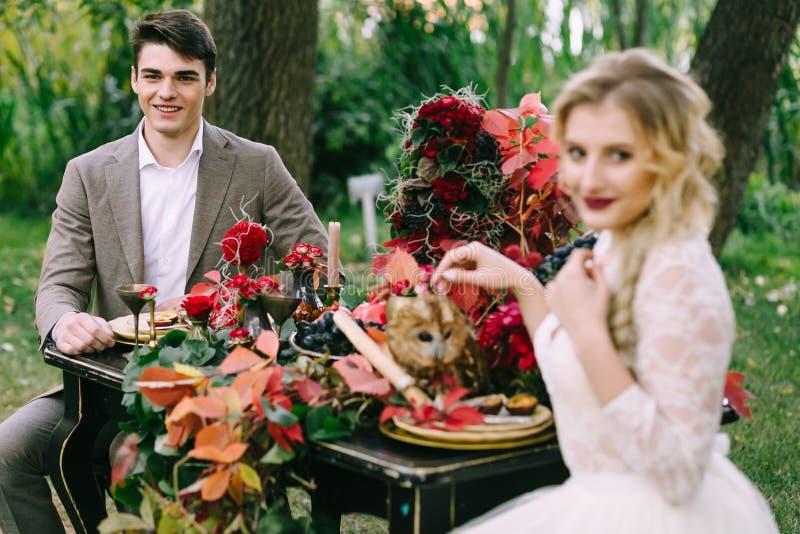 Den stiliga brudgummen sitter på den festliga tabellen på suddig brudbakgrund Höstbröllop arkivfoton