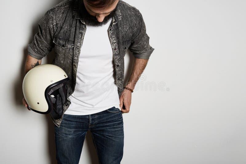 Den stiliga brutala skäggiga manliga modellen poserar i bomull för sommar för svart jeansskjorta och tom vit t-skjorta högvärdig  arkivfoton