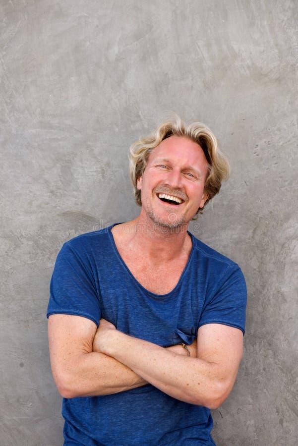 Den stiliga caucasian mannen som ler med armar, korsade mot väggen fotografering för bildbyråer