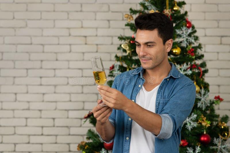Den stiliga caucasian mannen stirrar på hans exponeringsglas av vitt vin fotografering för bildbyråer
