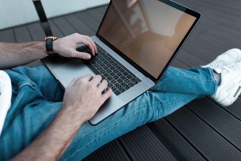 Den stiliga chefen för den unga mannen sitter på trägolv och arbetar på den moderna bärbara datorn som utomhus sitter royaltyfria foton