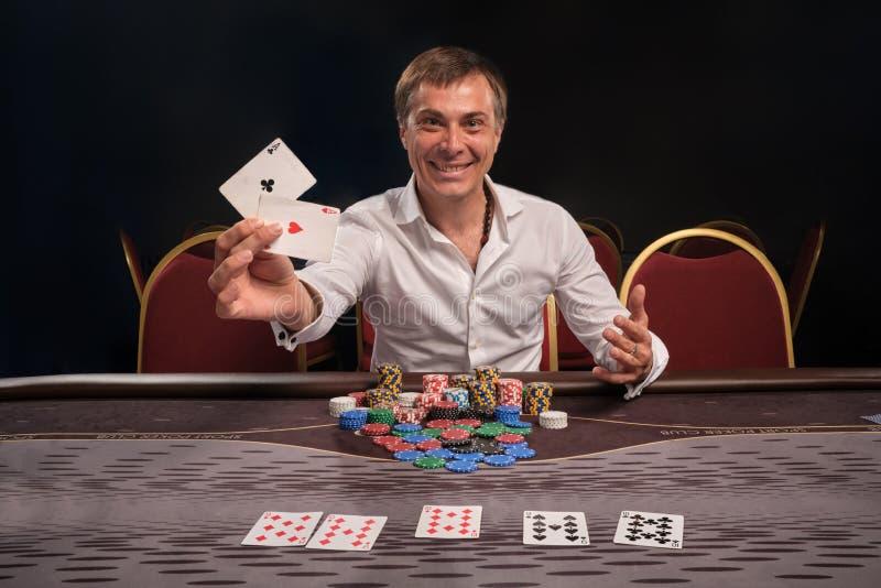 Den stiliga emotionella mannen spelar poker som sitter på tabellen i kasino royaltyfri fotografi