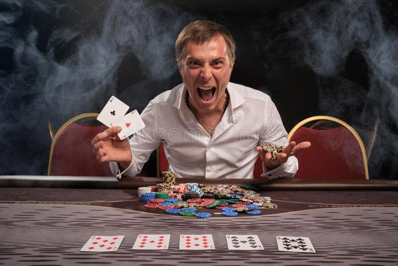 Den stiliga emotionella mannen spelar poker som sitter på tabellen i kasino royaltyfri bild