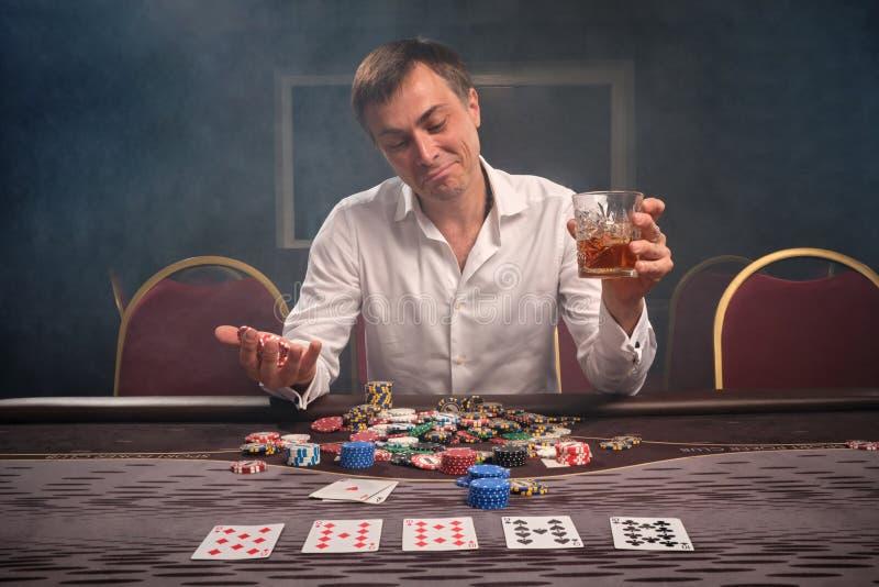 Den stiliga emotionella mannen spelar poker som sitter på tabellen i kasino arkivbilder