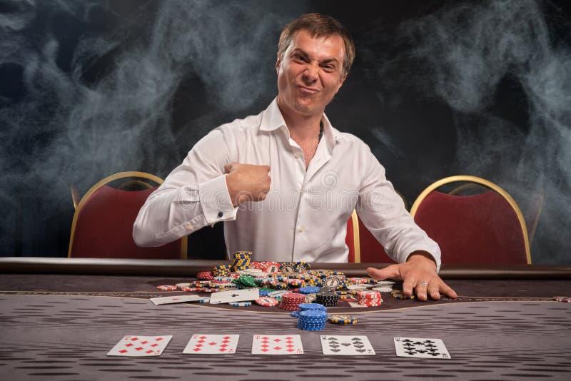 Den stiliga emotionella mannen spelar poker som sitter på tabellen i kasino royaltyfria bilder